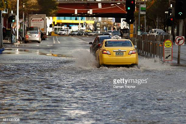 A taxi drives through flood water on Queensbridge st on June 24 2014 in Melbourne Australia Almost 80000 homes have lost power across Victoria due to...