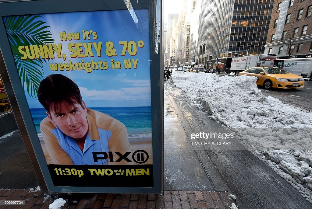 A taxi goes past a bus stop poster on 3rd Avenue January 25 2016 as New Yorkers return to work after the city was hit with a recordsetting snowfall...