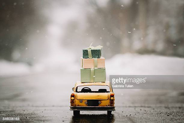 Taxi miniature carrying gifts boxes under the snow