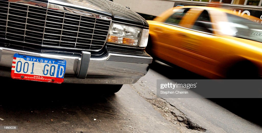 A taxi passes a car with diplomat license plates parked near the United Nations May 12 2003 in New York City The city launched a plan in 2002 to...