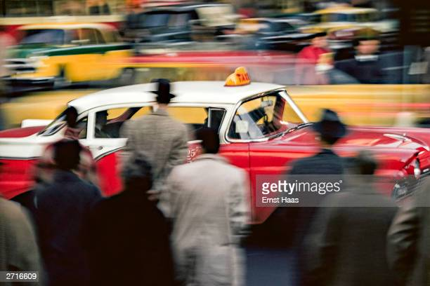 A taxi passes a crowd of pedestrians on a street in New York