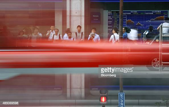 A taxi passes as pedestrians wait to cross a road in front of an electronic stock board outside a securities firm in Tokyo Japan on Monday Aug 24...