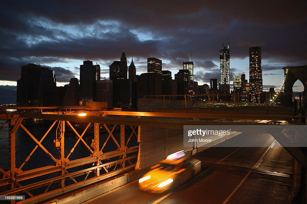 A taxi passes over the Brooklyn Bridge near the partially-lit skyline of lower Manhattan on November 3, 2012 in New York City.Although electricity has been restored to most of New York City, many areas remain without power five days after Superstorm Sandy.