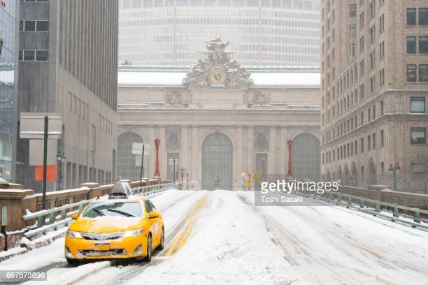 A taxi runs on Snowy Park Avenue during the snowstorm at Midtown Manhattan on Mar. 14 2017. Grand Central Terminal can be seen behind.