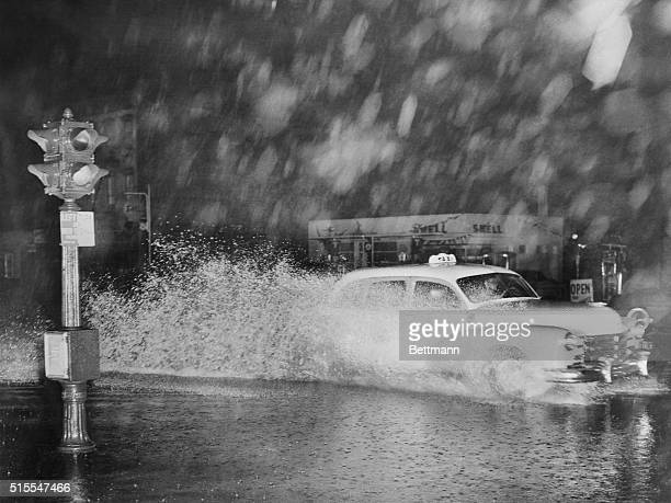A taxi sends up a big bow wave and leaves a wake of spray as it shoots through a flooded street at Atlantic and Grand Avenues Brooklyn as the tail of...