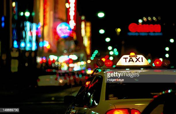 Taxi sign and coloured street lights.