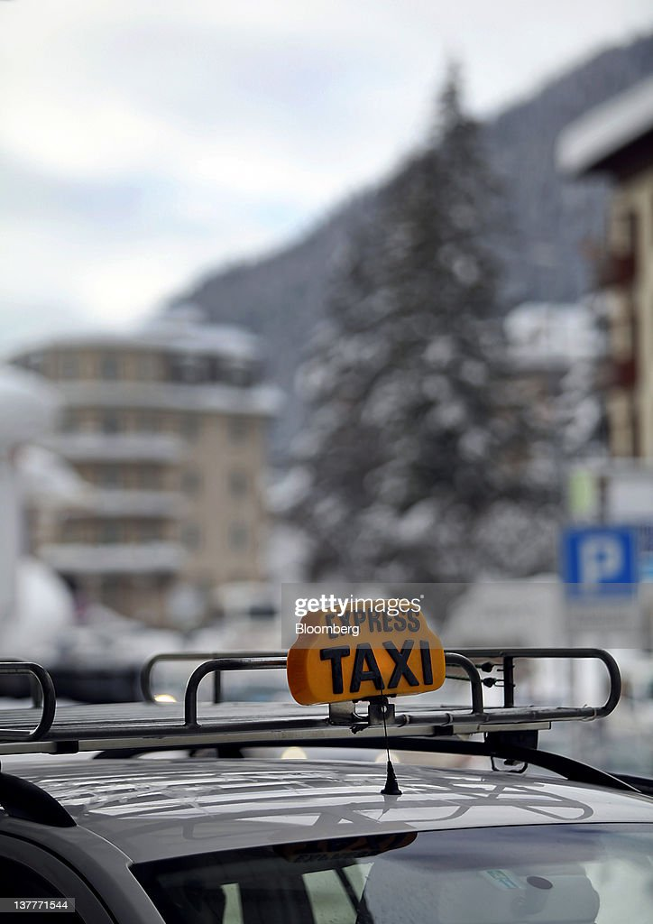A taxi sign is displayed on top of a vehicle outside the Davos Platz train station during day two of the World Economic Forum (WEF) in Davos, Switzerland, on Thursday, Jan. 26, 2012. The 42nd annual meeting of the World Economic Forum will be attended by about 2,600 political, business and financial leaders at the five-day conference. Photographer: Chris Ratcliffe/Bloomberg via Getty Images