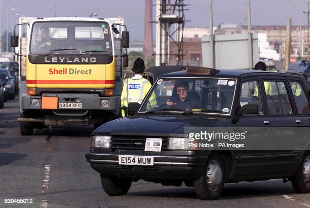 A taxi temporarily holds up a Shell lorry outside the Stanlow Oil refinery in Cheshire where farmers and road hauliers are protesting against high...