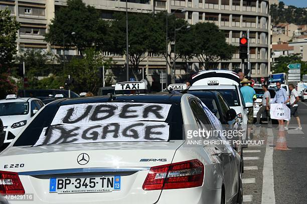 A Taxi with a banner that reads 'Uber get out' is seen during a protest in the southern city of Marseille on June 25 2015 as taxi drivers demonstrate...