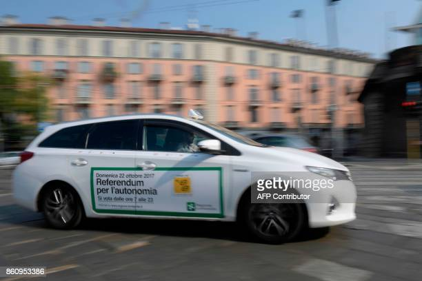 A taxi with a sticker announcing a referendum in Italy's northern region of Lombardy to request more autonomy from central government passes in a...
