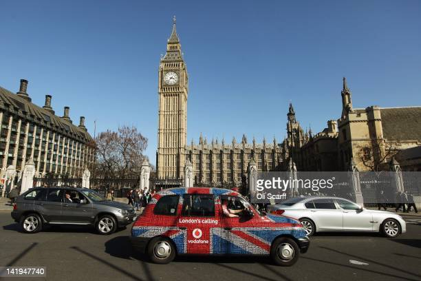 A taxi with a Union Flag livery drives through Parliament Square on March 26 2012 in London England