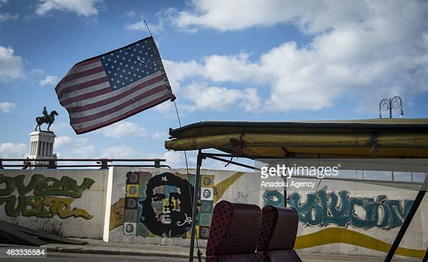 A taxi with US flag passes by a wall with the graffiti portrait of Che Guevara in Havana Venezuela on February 12 2015 Cubans continue their daily...