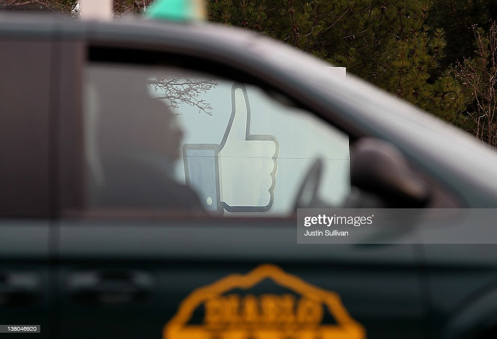 A taxicab passes by a sign standing in front of the Facebook headquarters on February 1, 2012 in Menlo Park, California. Facebook is expected to file for its first initial public offering today seeking to raise at least $5 billion.