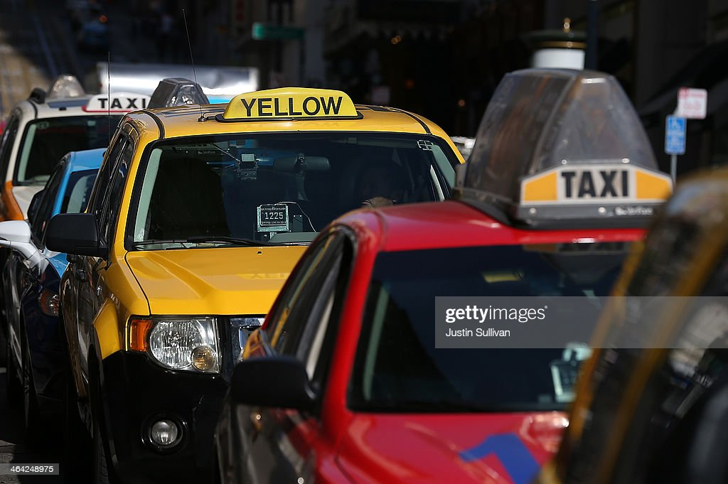 Taxicabs wait for fares in front of the St Francis Hotel on January 21 2014 in San Francisco California As ridesharing services like Lyft Uber and...