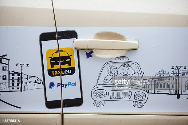 A Taxieu cab hire smart phone app advertisement and the PayPal online payment system logo sit on the side of a taxi operated by Leipold Taxibetrieb...