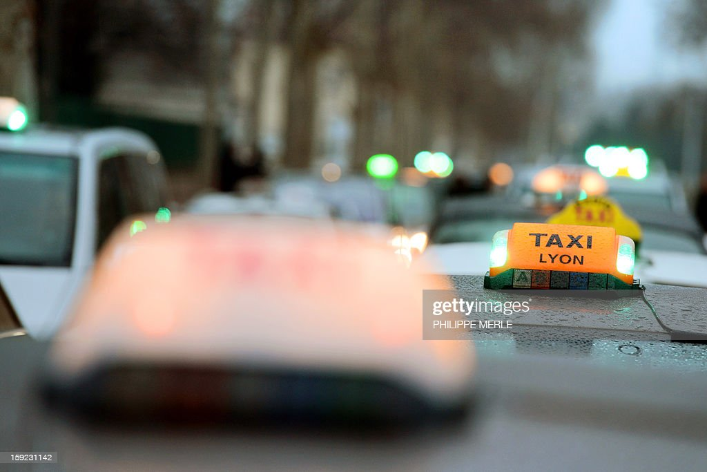 Taxis block a street in Lyon, on January 10, 2013, as they take part in a nationwide demonstration to protest against legislative changes concerning the transport of sick and incapacitated passengers. AFP PHOTO / PHILIPPE MERLE