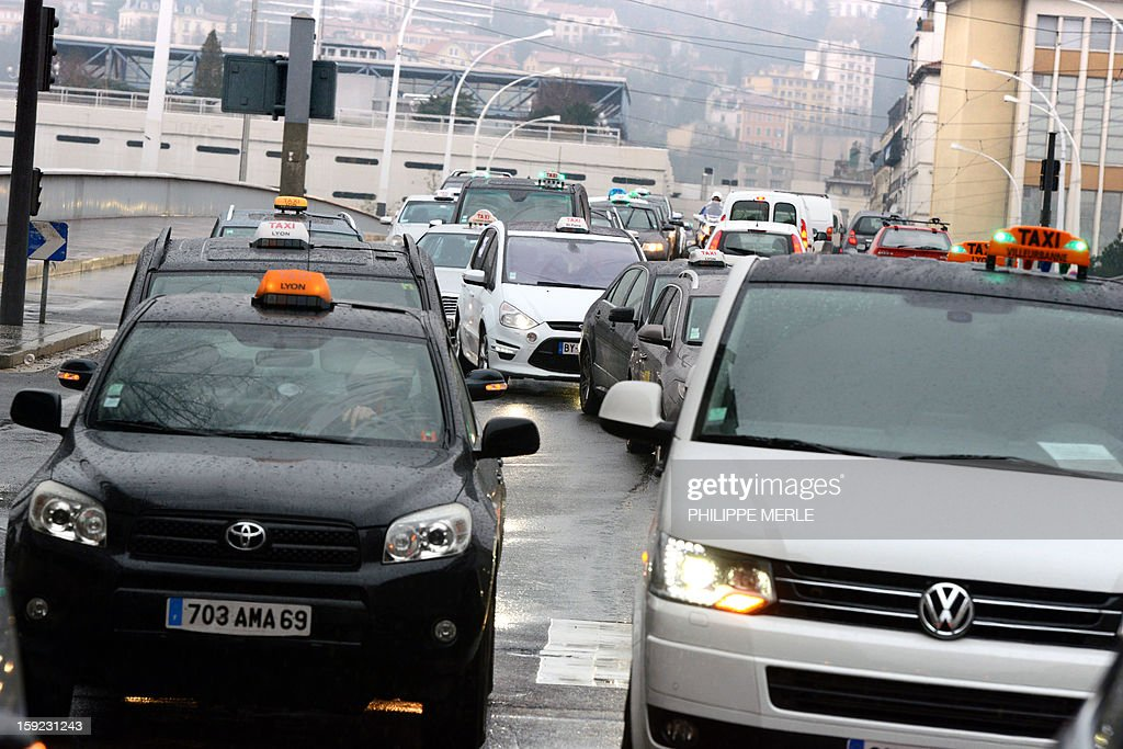 Taxis block a street in Lyon, on January 10, 2013, as they take part in a nationwide demonstration to protest against legislative changes concerning the transport of sick and incapacitated passengers.
