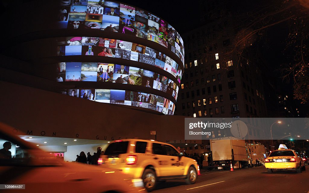 Taxis drive by as the top 25 submissions to the YouTube Play: A Biennial of Creative Video exhibit and event are projected onto the exterior of the Guggenheim Museum in New York, U.S. on Thursday, Oct. 21, 2010. Google Inc. showcased videos at the museum as part of YouTube Play, a contest for users of the company's video site. Google's dalliance with the fine arts is part of a broader initiative to attract top advertisers and additional users to YouTube, the most visited U.S. video-sharing site. Photographer: Jeremy Bales/Bloomberg via Getty Images