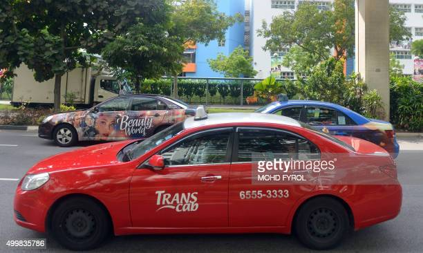 Taxis drive down a street in Singapore on December 4 2015 US ridesharing service Lyft on December 3 announced an expansion of its alliances with...