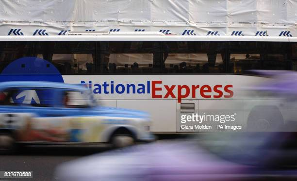 Taxis drive past a parked National Express coach near Victoria coach station London