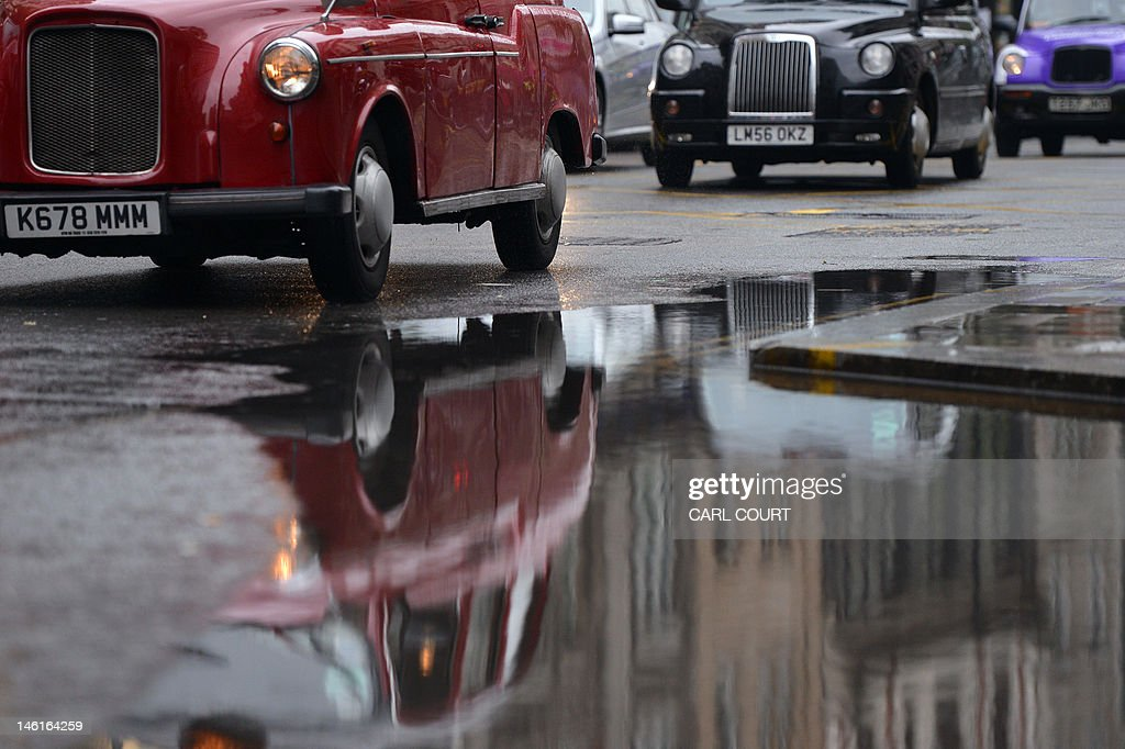 Taxis drive past a puddle left by persistent rain in central London on June 11, 2012.