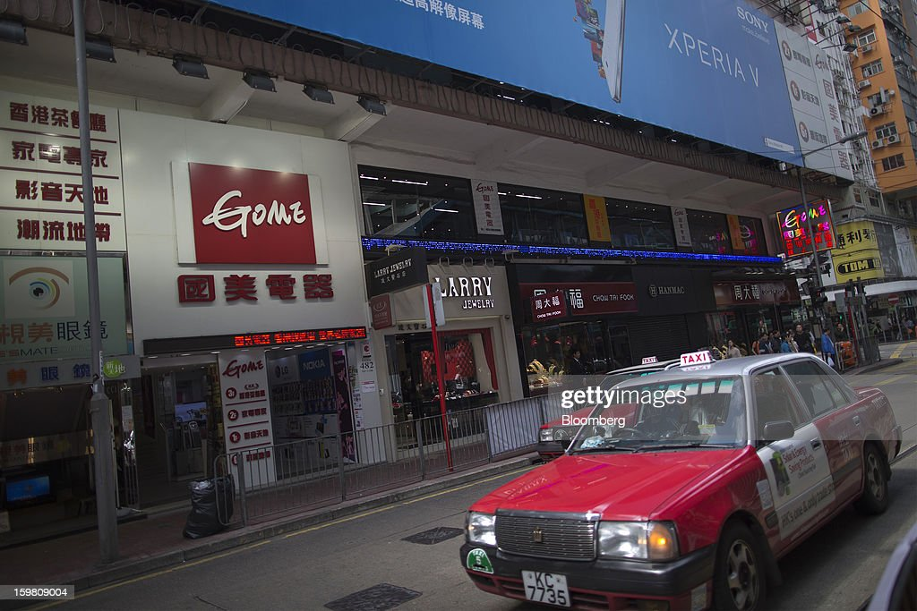 Taxis drive past the entrance of a Gome-branded store in the shopping district of Causeway Bay in Hong Kong, China, on Monday, Jan. 21, 2012. Gome Electrical Appliances Holding Ltd.'s stocks tumbled in Hong Kong after the company confirmed a report it is closing Gome-branded stores in the city. Photographer: Jerome Favre/Bloomberg via Getty Images