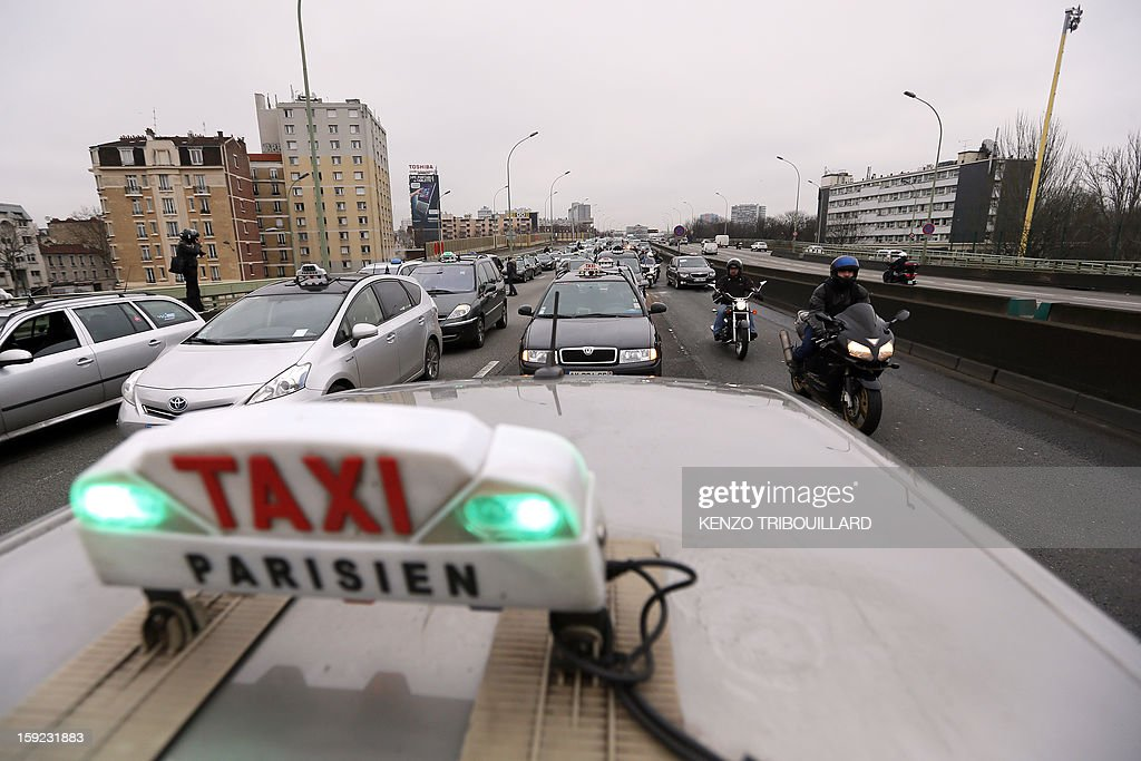 Taxis drivers on strike take part in a nationwide demonstration on a highway near Paris on January 10, 2013 to protest against legislative changes concerning the transport of sick and incapacitated passengers. AFP PHOTO / KENZO TRIBOUILLARD