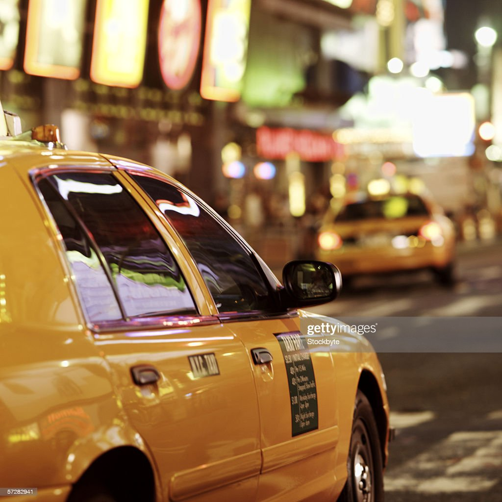 Taxis driving through times square in New York city : Stock Photo