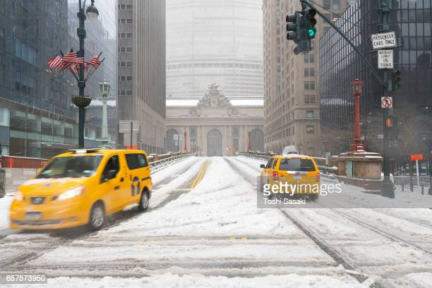 Taxis run on Snowy Park Avenue during the snowstorm at Midtown Manhattan on Mar. 14 2017. Grand Central Terminal can be seen behind.