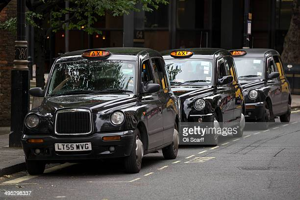 Taxis wait on a rank in Westminster on June 2 2014 in London England The controversial mobile application 'Uber' which allows users to hail...