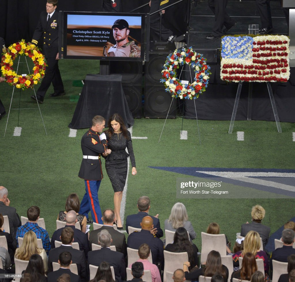 Taya Kyle is escorted back to her seat after addressing the audience at the funeral of her husband, Chris Kyle, at Cowboys Stadium in Arlington, Texas, Monday, February 11, 2013. Kyle was a highly decorated former Navy SEAL sniper who was shot and killed at a shooting range last week.