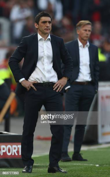 Tayfun Korkut head coach of Leverkusenlooks on with Andries Jonker head coach of Wolfsburg behind him during the Bundesliga match between Bayer 04...