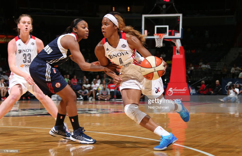 Tayler Hill of the Washington Mystics drives against Renee Montgomery of the Connecticut Sun at the Verizon Center on August 11 2013 in Washington DC...