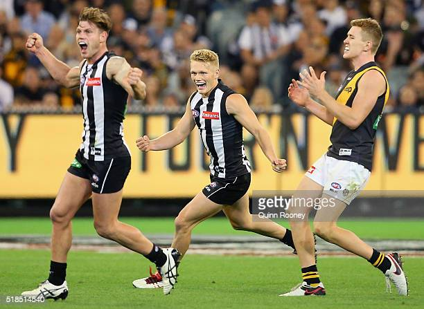 Taylor Adams and Adam Treloar of the Magpies celebrate winning as Jacob Townsend of the Tigers looks dejected after losing the round two AFL match...
