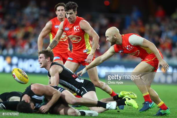 Taylor Adams of the Magpies handballs while Alex Fasolo is injured during the round 17 AFL match between the Gold Coast Suns and the Collingwood...