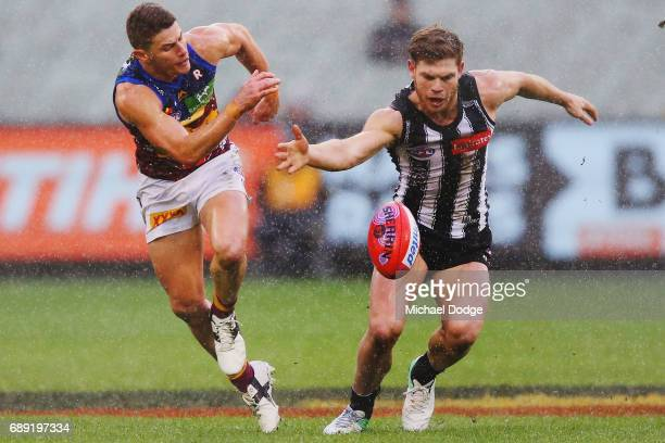 Taylor Adams of the Magpies wins the ball against Dayne Zorko of the Lions during the round 10 AFL match between the Collingwood Magpies and Brisbane...