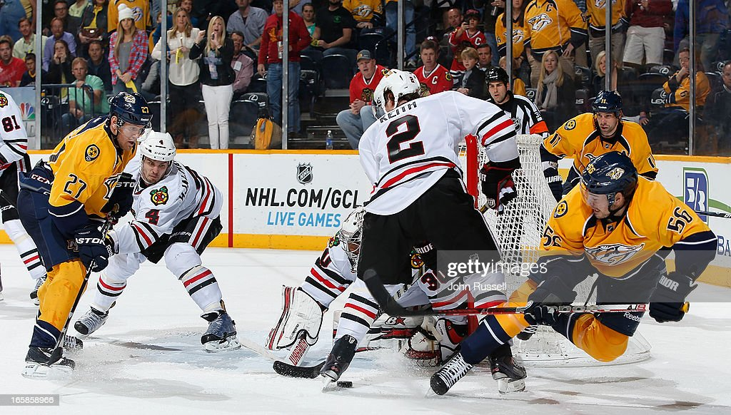 Taylor Beck #56 of the Nashville Predators attempts to center the puck against Ray Emery #30 and Duncan Keith #2 of the Chicago Blackhawks during an NHL game at the Bridgestone Arena on April 6, 2013 in Nashville, Tennessee.