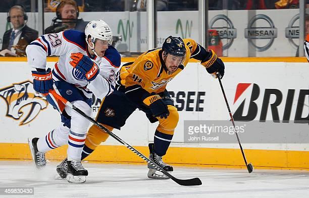 Taylor Beck of the Nashville Predators skates against Leon Draisaitl of the Edmonton Oilers at Bridgestone Arena on November 27 2014 in Nashville...