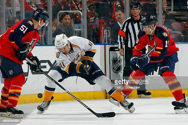 Taylor Beck of the Nashville Predators tangles with Brian Campbell and Scottie Upshall of the Florida Panthers at the BBT Center on February 8 2015...
