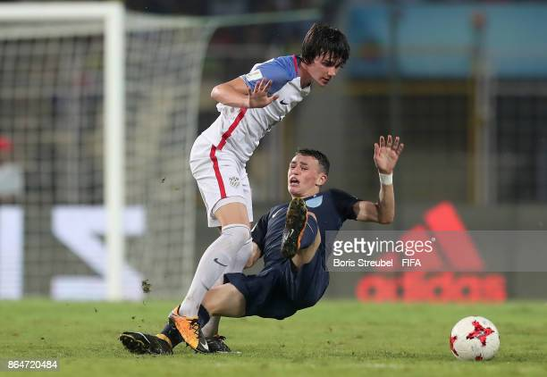 Taylor Booth of the United States is challenged by Philip Foden of England during the FIFA U17 World Cup India 2017 Quarter Final match between USA...