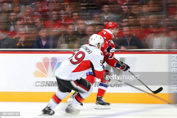 Taylor Chorney of the Washington Capitals skates past David Dziurzynski of the Ottawa Senators in the first period at Verizon Center on December 16...