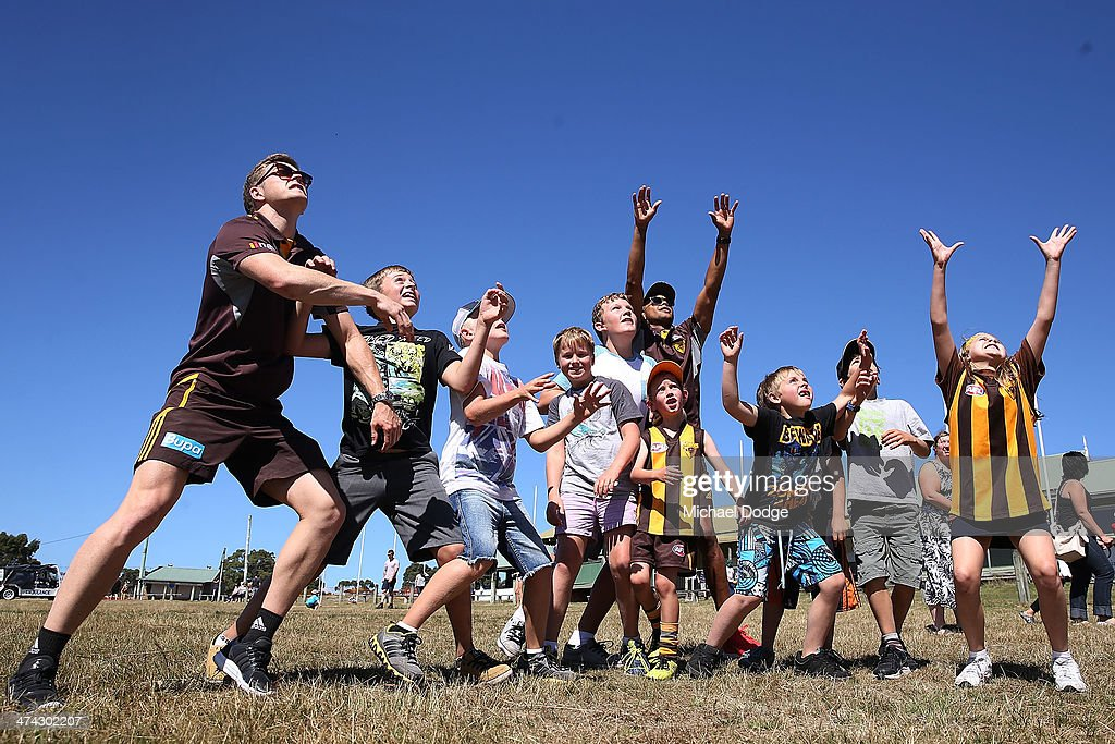 Taylor Duryea (L) and Dayle Garlett play with kids at the Bream Creek Oval during the Hawthorn Hawks AFL Tasmania Community Camp on February 23, 2014 in Bream Creek, Australia.