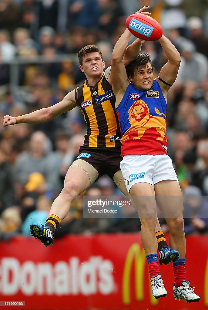 Taylor Duryea (L) of the Hawks and Jed Adcock of the Lions contest for the ball during the round 14 AFL match between the Hawthorn Hawks and the Brisbane Lions at Aurora Stadium on June 30, 2013 in Launceston, Australia.