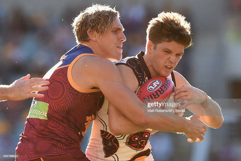 Taylor Duryea of the Hawks is tackled by Tom Bell of the Lions during the round 10 AFL match between the Brisbane Lions and the Hawthorn Hawks at The Gabba on May 28, 2016 in Brisbane, Australia.