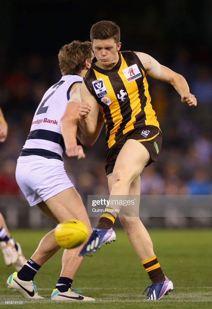Taylor Duryea of the Hawks kicks whilst being bumped by Billie Smedts of the Cats during the VFL Grand Final match between the Box Hill Hawks and the Geelong Cats at Etihad Stadium on September 22, 2013 in Melbourne, Australia.