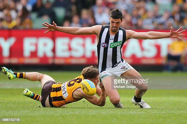 Taylor Duryea of the Hawks tackles Scott Pendlebury of the Magpies during the round 23 AFL match between the Hawthorn Hawks and the Collingwood...
