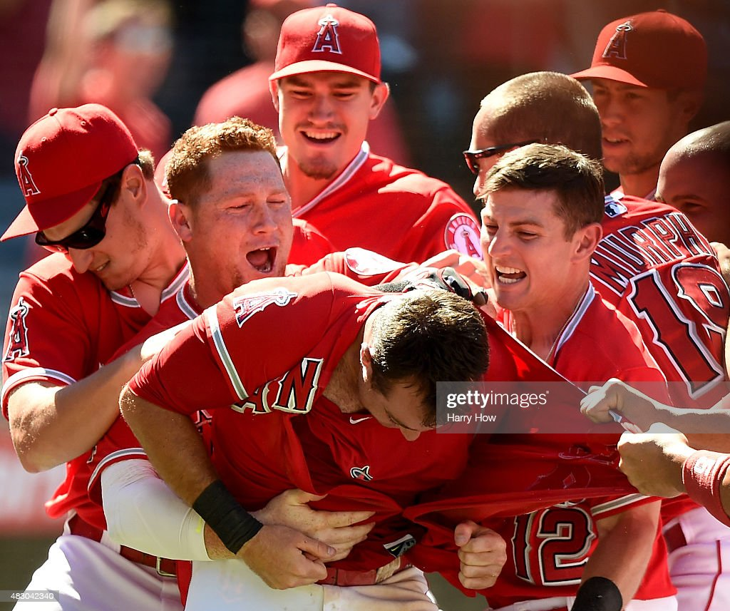 Taylor Featherston #8 of the Los Angeles Angels is mobbed by <a gi-track='captionPersonalityLinkClicked' href=/galleries/search?phrase=Kole+Calhoun&family=editorial&specificpeople=9008672 ng-click='$event.stopPropagation()'>Kole Calhoun</a> #56 and <a gi-track='captionPersonalityLinkClicked' href=/galleries/search?phrase=Johnny+Giavotella&family=editorial&specificpeople=7512348 ng-click='$event.stopPropagation()'>Johnny Giavotella</a> #12 in response to his run from a wild pitch during the bottom of the ninth inning to win the game 4-3 over the Cleveland Indians at Angel Stadium of Anaheim on August 5, 2015 in Anaheim, California.