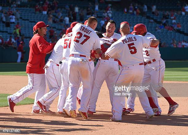 Taylor Featherston of the Los Angeles Angels of Anaheim is mobbed by teammates while celebrating after hitting a walkoff RBI to defeat the Houston...