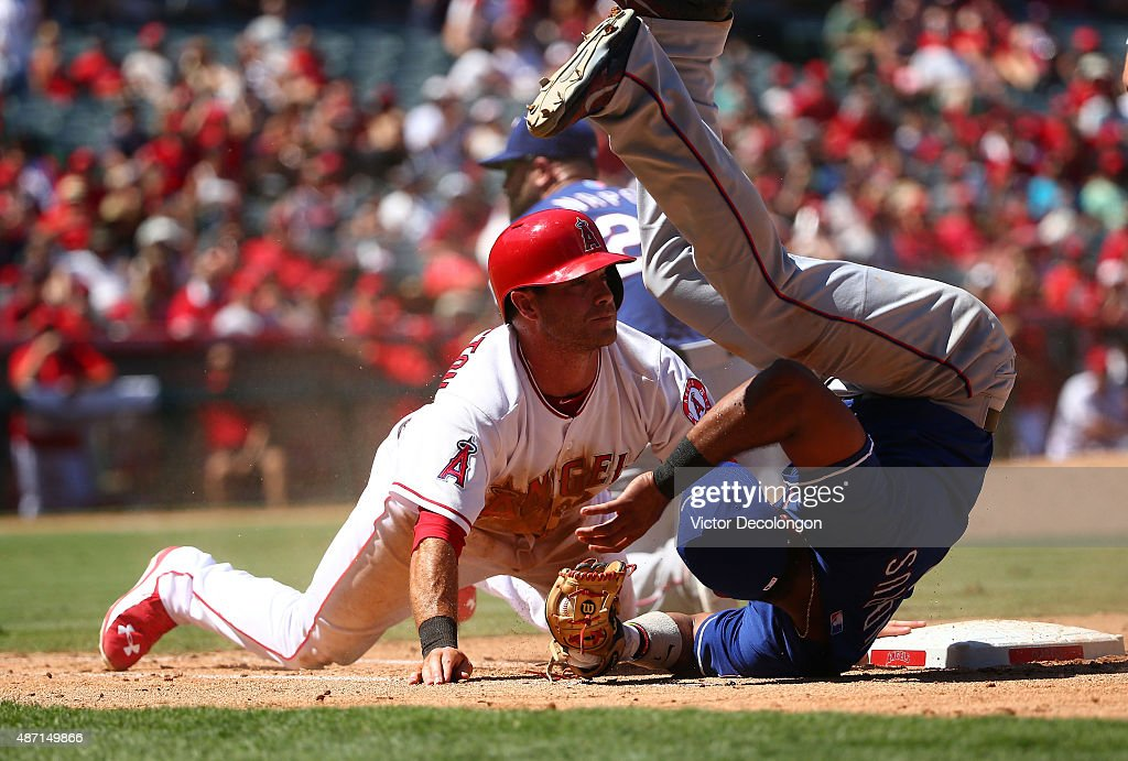 Taylor Featherston of the Los Angeles Angels of Anaheim looks to the umpire for the call as Elvis Andrus of the Texas Rangers rolls on his shoulder...