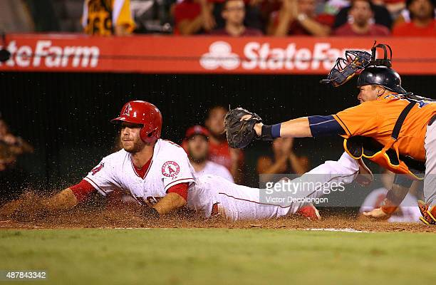 Taylor Featherston of the Los Angeles Angels of Anaheim slides into home plate as catcher Hank Conger of the Houston Astros holds up the tag in the...